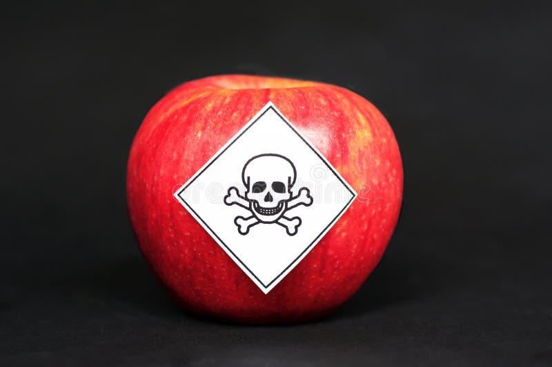 农药残留的概念在农业食品的危险对人,显示与毒物标志的一个红色苹果 免版税库存照片