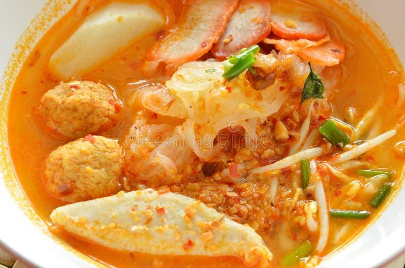冠上切片的稀薄的米线烤猪肉和鱼丸在汤姆汤 图库摄影