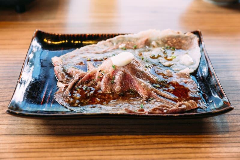 冠上用新鲜的大蒜的被接触的半生半熟切的地道A5等级日本Wagyu牛肉寿司 库存照片