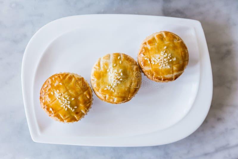 冠上用白色芝麻的新鲜的被烘烤的广东BBQ大馅饼顶视图在大理石顶面桌上的白色板材服务 免版税库存照片