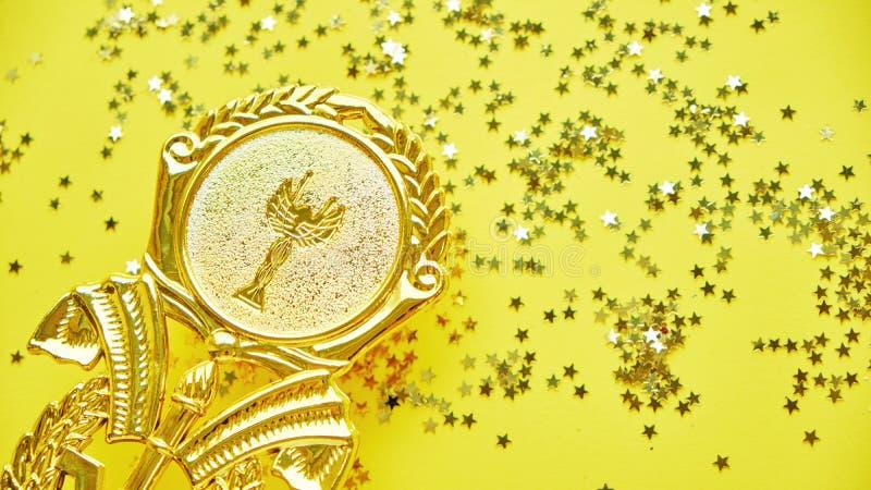 冠军金在黄色背景的杯子战利品 简单派样式,庆祝胜利概念 并且金黄星  库存照片