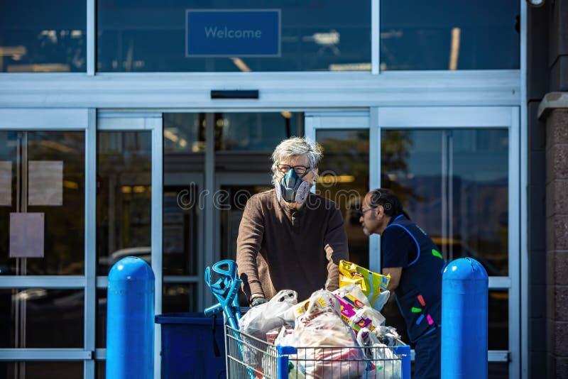 冠状病毒流行期间穿呼吸机口罩离开杂货店的男子 免版税图库摄影