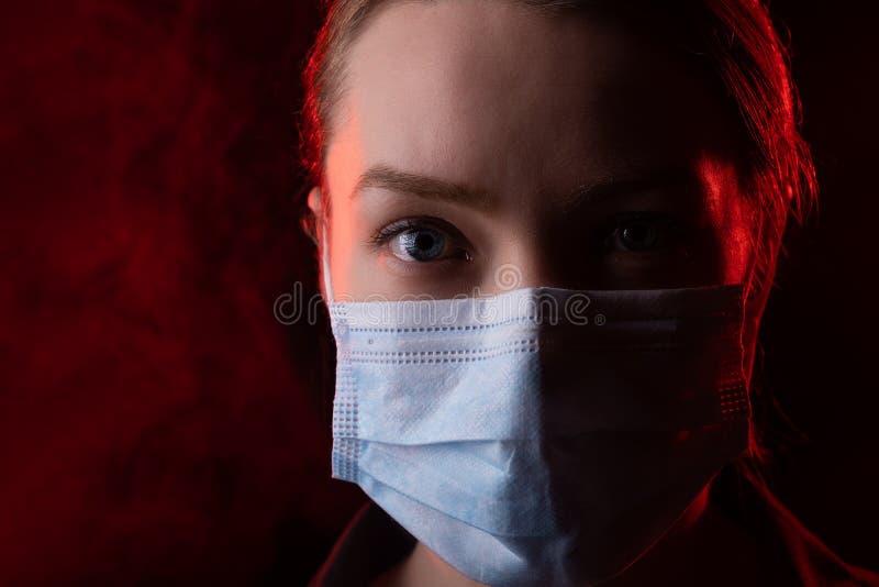 冠状病毒,黑色背景中戴面具的女孩 书名是关于美国爆发冠状病毒, 库存照片