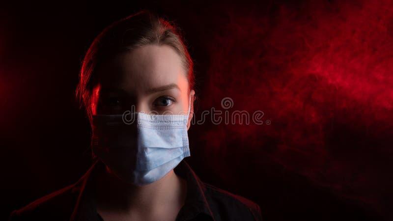 冠状病毒,黑色背景中戴面具的女孩 书名是关于美国爆发冠状病毒, 库存图片
