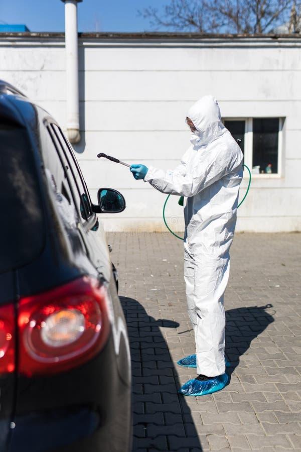 冠状病毒 防护服和口罩中的消毒剂在室外喷洒汽车消毒剂 库存图片