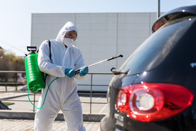 冠状病毒 防护服和口罩中的消毒剂在室外喷洒汽车消毒剂 免版税图库摄影