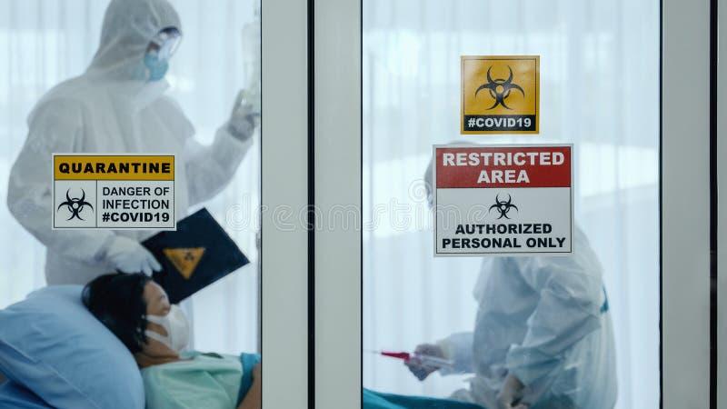 冠状病毒covid-19在医院检疫室窗口上的检疫和突发警报标志,疾控专家试行 库存图片