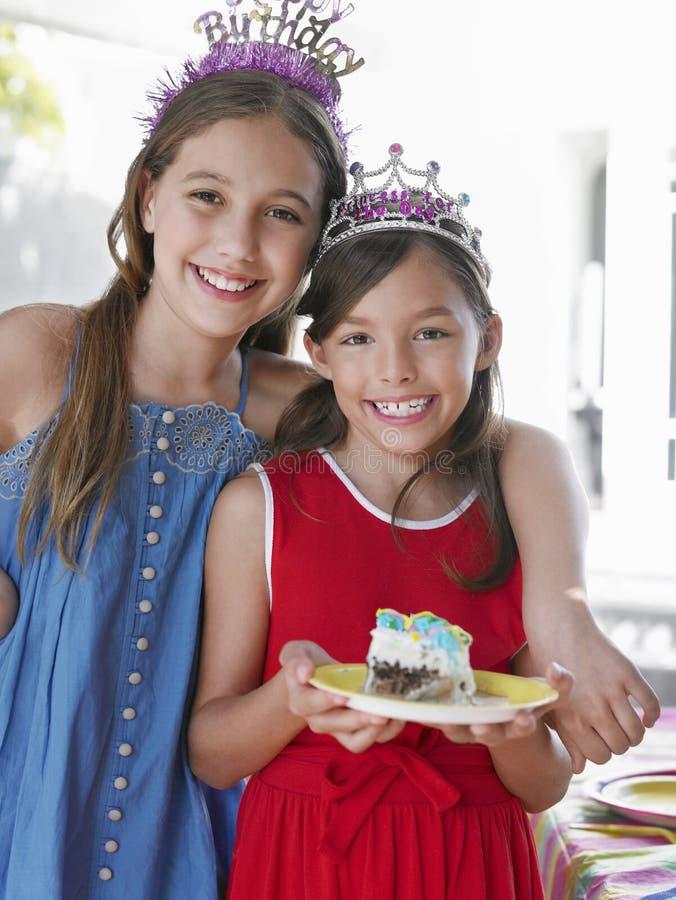冠状头饰的两个微笑的女孩 库存图片