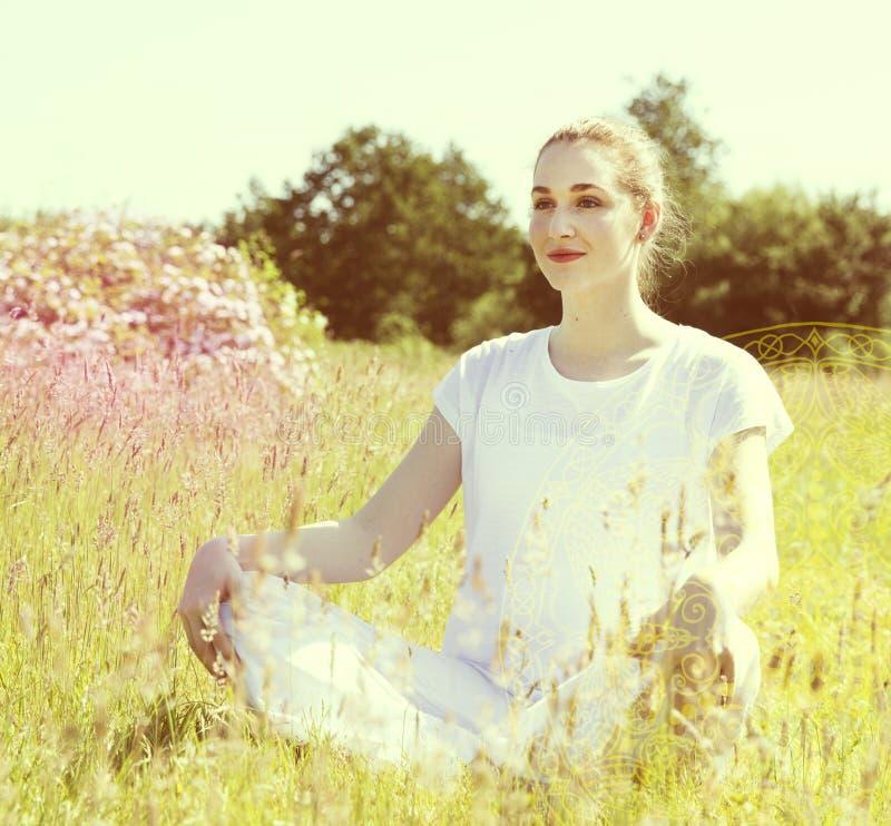 冥想发光的年轻瑜伽的妇女思考,晴朗的减速火箭的作用 免版税图库摄影