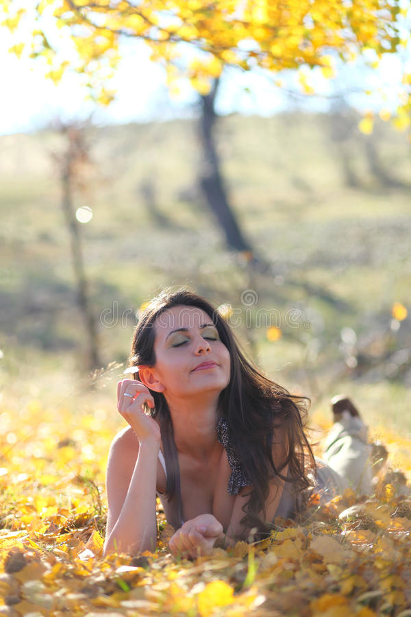 冥想在叶子的少妇 免版税库存图片