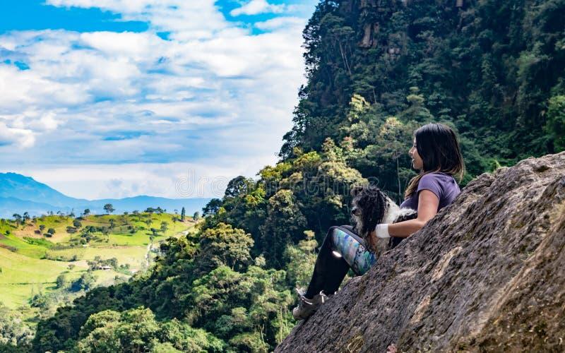 冥想在岩石,第一pho的妇女和她的狗天际 库存图片