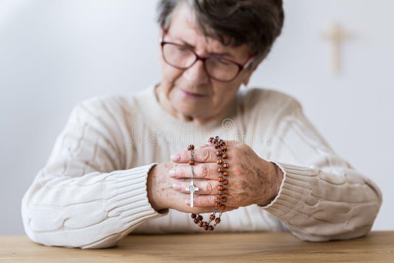 冥想有念珠的年长妇女 库存照片