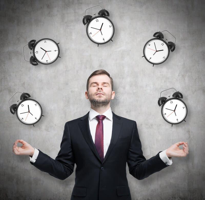 冥想的商人考虑关于时间安排 正式衣服的人由闹钟围拢 有骗局 免版税图库摄影