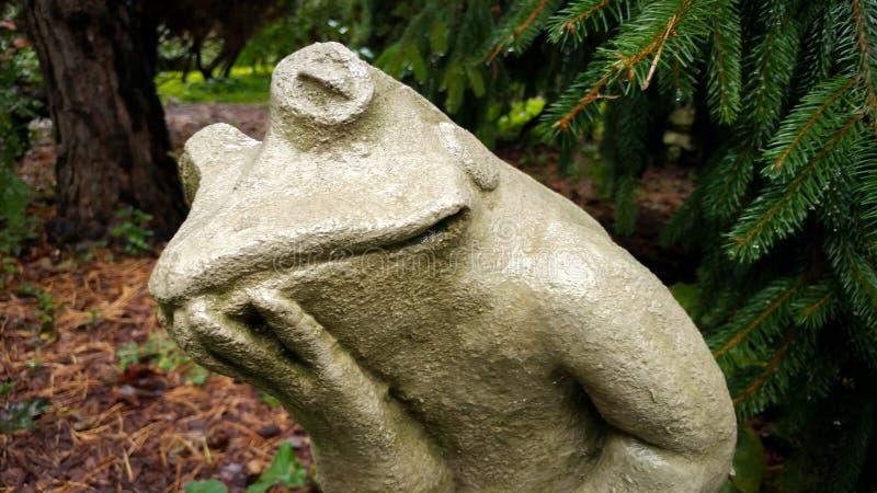 冥想青蛙水泥雕象在庭院里 免版税库存图片