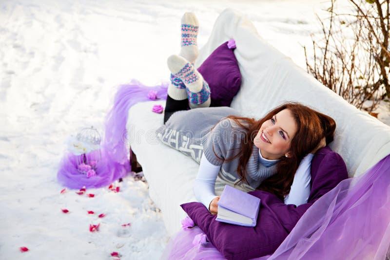 冬天、森林、长沙发和妇女有书的 库存图片
