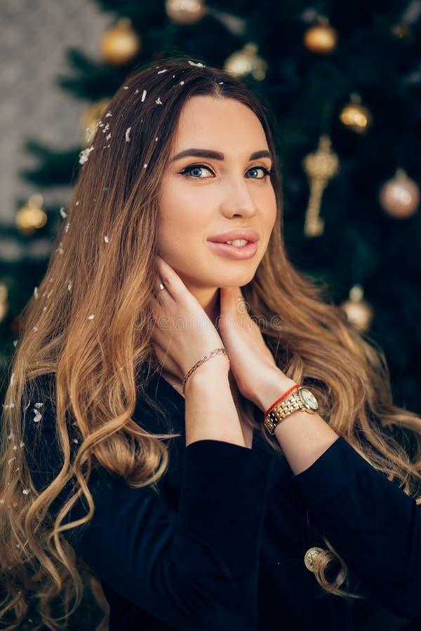 冬天一名美丽的微笑的妇女的特写镜头画象由圣诞树的 假日、庆祝和人们 免版税库存图片