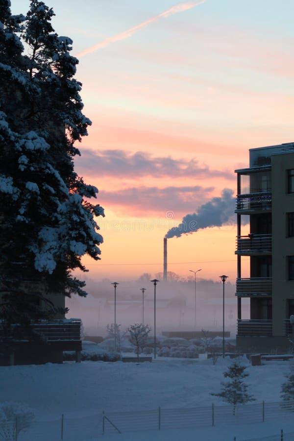 冬天与烟囱的早晨日出 免版税库存照片