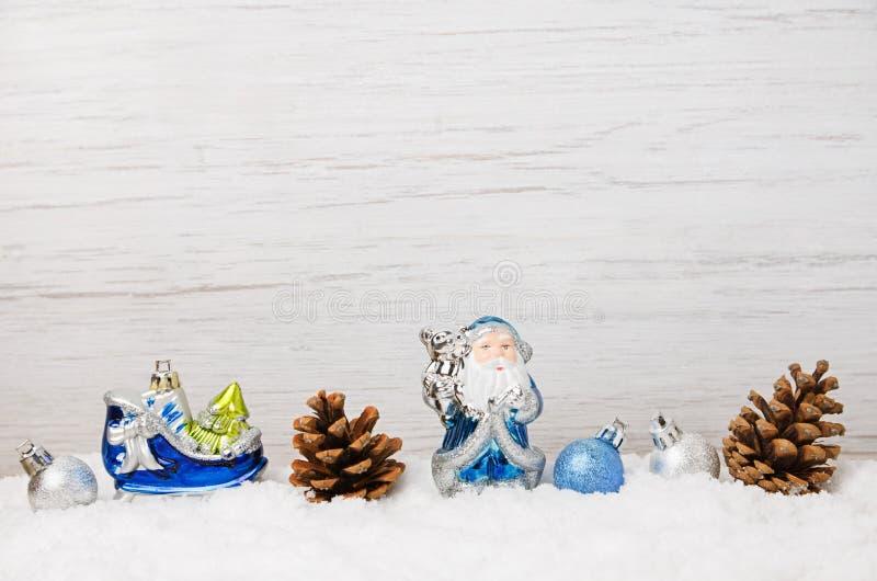 冬天与蓝色圣诞装饰的雪场面在雪,轻的木背景 免版税库存照片