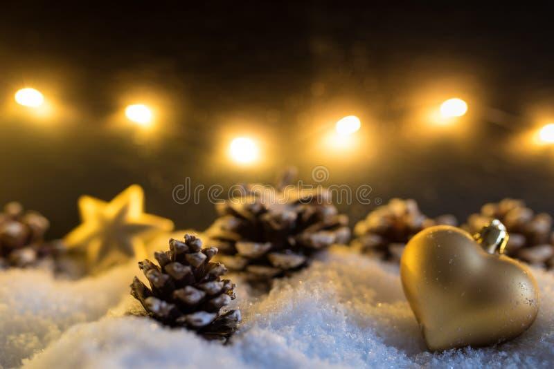 冬天与金黄心形的圣诞树装饰品和杉木锥体的圣诞节装饰 库存图片