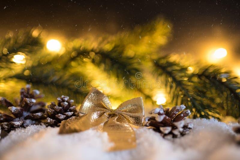 冬天与金黄礼物丝带、冷杉分支和锥体的圣诞节装饰 免版税库存图片