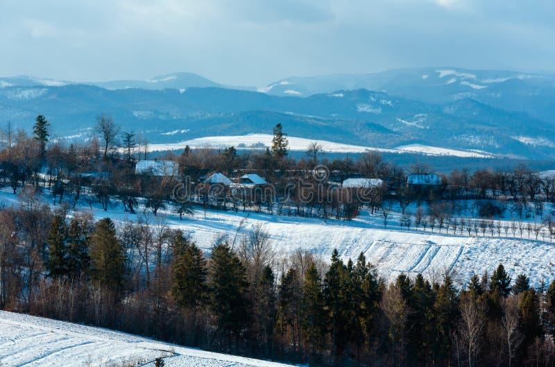 冬天与领域和村庄的山风景 库存照片