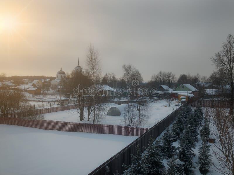 冬天农村路和树在雪和太阳在日出 免版税库存照片