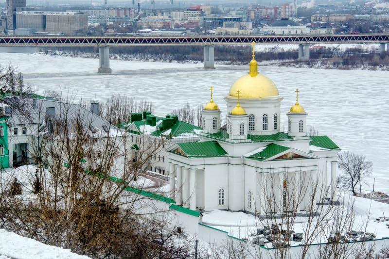 冬天冻河河岸的美丽的大白色教会  免版税库存图片