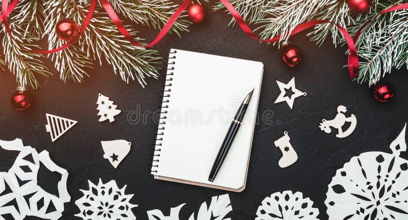 冬天卡片 染黑石背景 冷杉分支用球和红色松驰装饰了 顶视图 文本的空间在笔记本 免版税库存图片