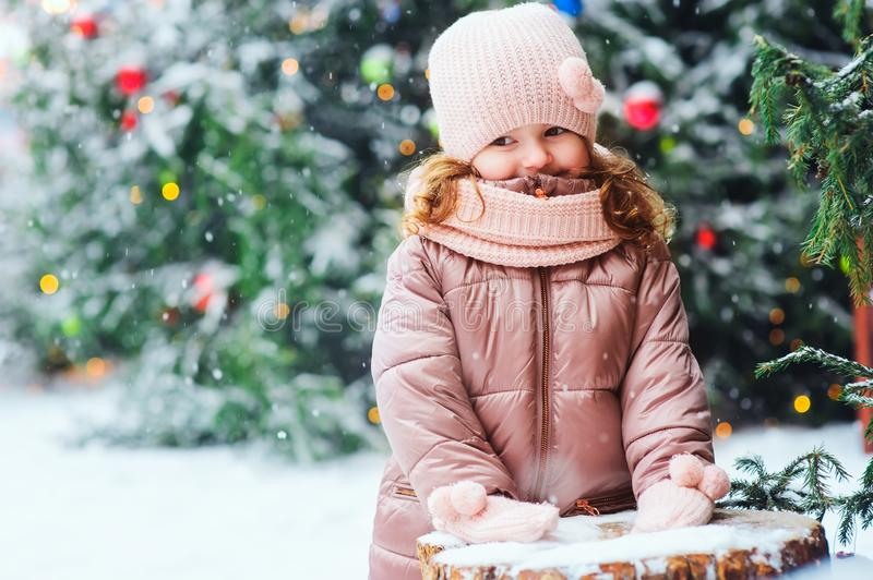 冬天和圣诞节画象愉快女婴走室外在多雪的天,在假日装饰的城市 免版税库存照片