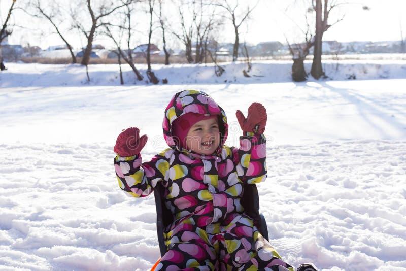 冬天和多雪的背景的孩子 做雪天使,当说谎在雪时 库存图片