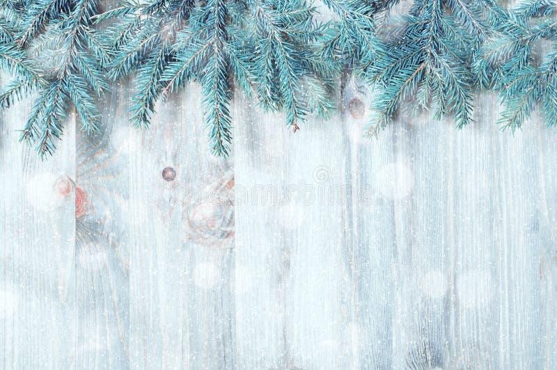 冬天圣诞节和新年背景 蓝色杉树分支与在木背景的冬天雪花 免版税库存照片
