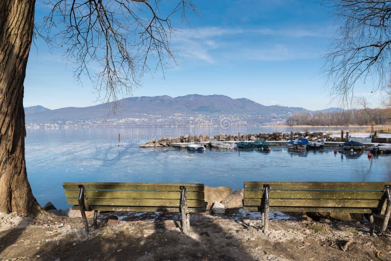 冬天在意大利北部 结冰的Varese湖和园地dei费奥里,山在背景中,从卡扎戈布拉比亚村庄,意大利 免版税库存图片