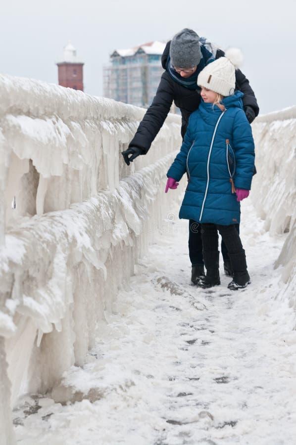 冬天在Darlowo海滩的家庭步行 免版税库存图片
