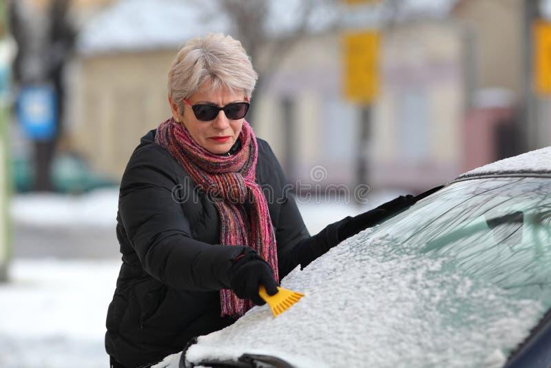 冬天场面,司机清洁挡风玻璃og汽车 库存图片