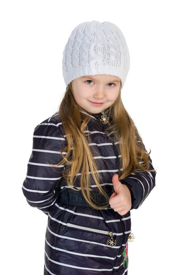 冬天外套的小女孩举行她的赞许 库存照片