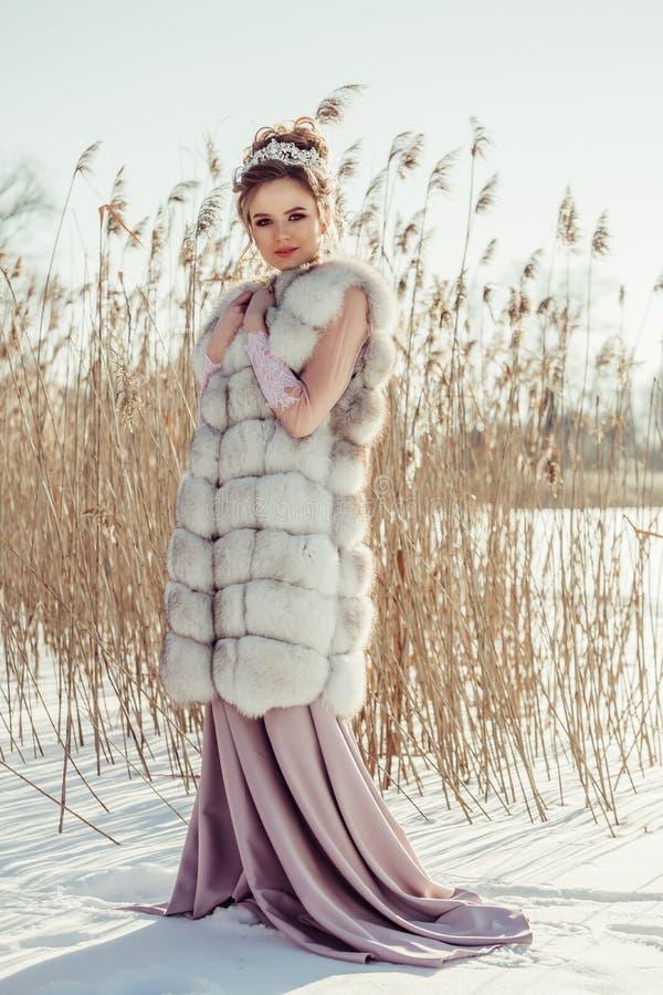 冬天外套的美丽的女孩有冠和花束的 免版税库存图片