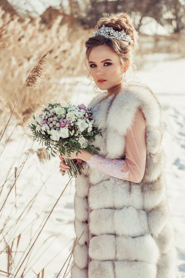 冬天外套的美丽的女孩有冠和花束的 库存照片