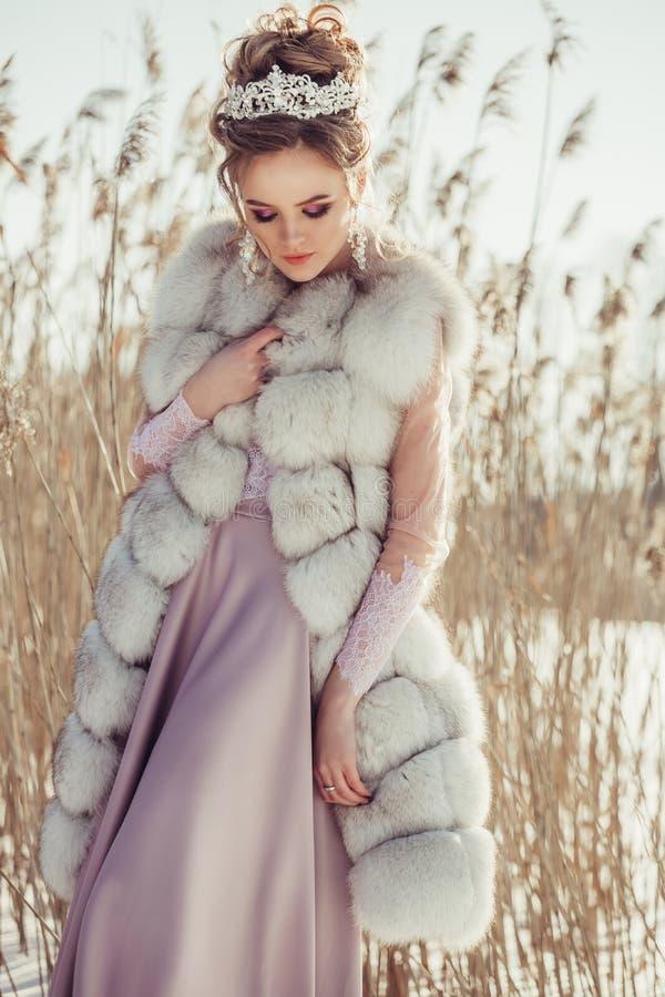 冬天外套的美丽的女孩有冠和花束的 免版税图库摄影