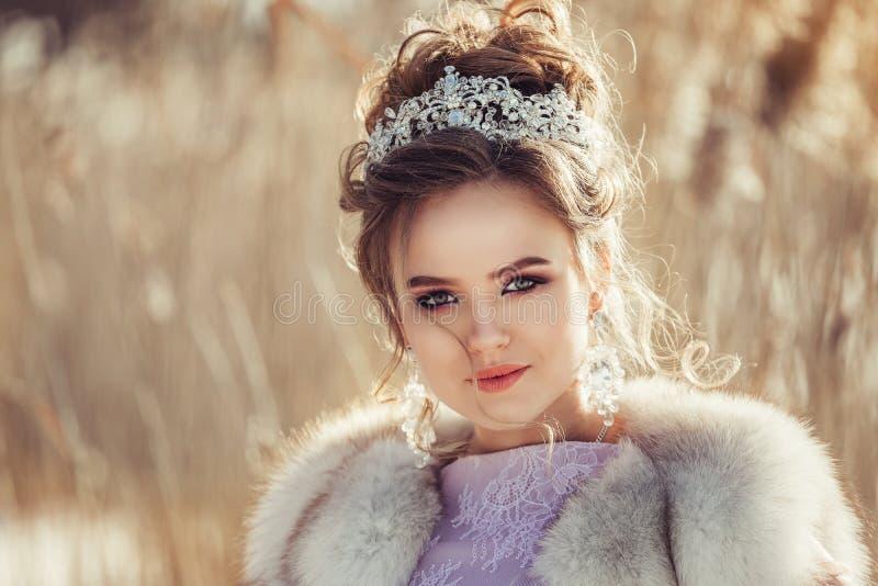 冬天外套的美丽的女孩有冠和花束的 免版税库存照片