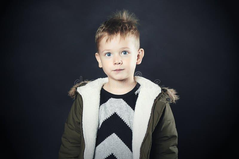 冬天外套的滑稽的孩子 方式孩子 孩子 卡其色的附头巾皮外衣 有大眼睛的小男孩 免版税库存图片