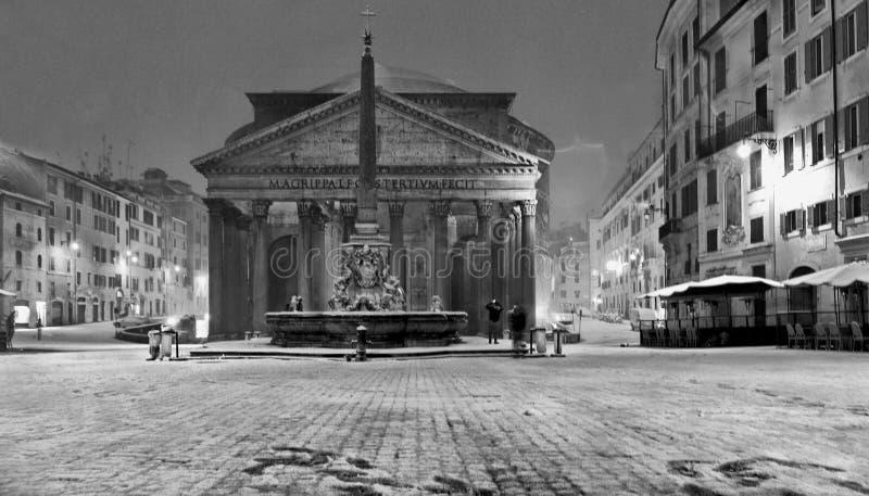 冬天夜在有雪飞雪和万神殿寺庙教会的罗马与金黄光,意大利的空的正方形的 库存图片