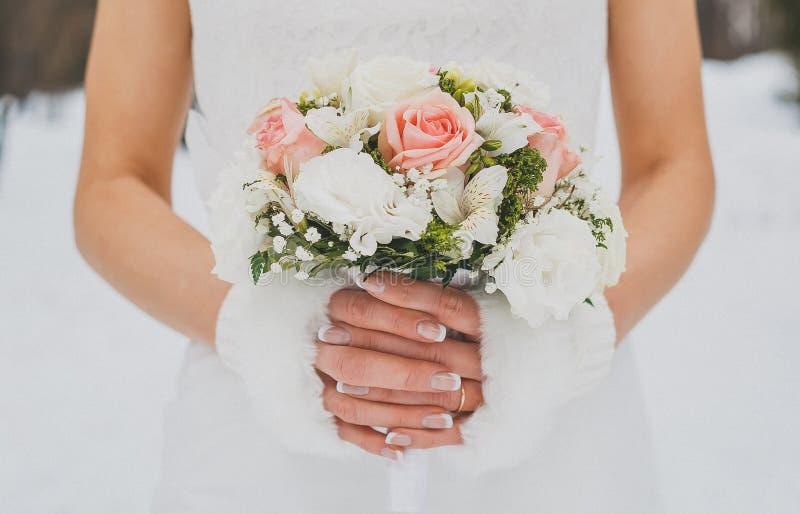 冬天婚礼摄影 新娘花束在新娘的手上 r 桃红色玫瑰花束  免版税库存图片