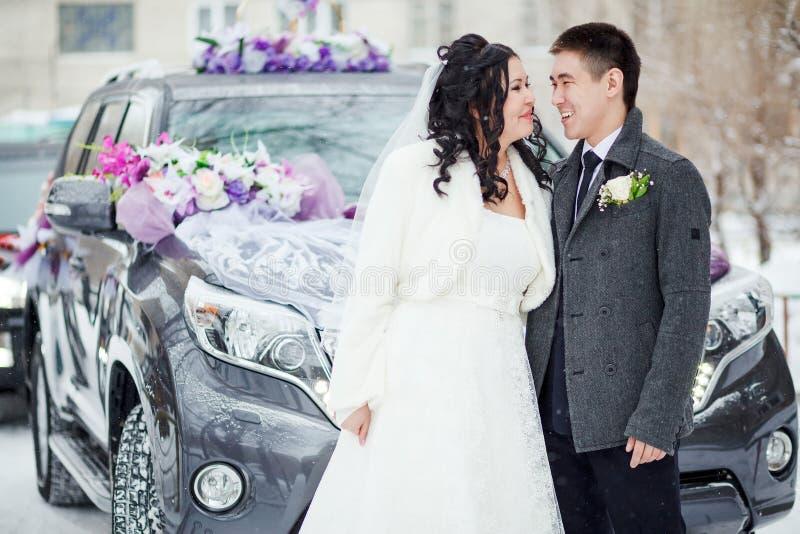 冬天婚礼,在装饰的汽车前的愉快的夫妇在一条多雪的街道上 新娘每新郎查找其他 库存图片