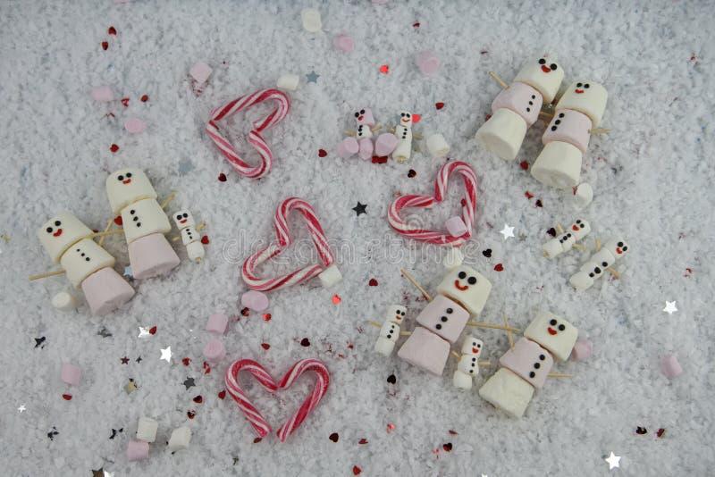 冬天季节圣诞节使用蛋白软糖的食物摄影塑造了作为在雪的微笑以愉快冰的雪人与爱心脏 库存照片