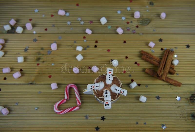 冬天季节摄影与热巧克力杯子和微型蛋白软糖的食物和饮料图象塑造了作为愉快的雪人 图库摄影