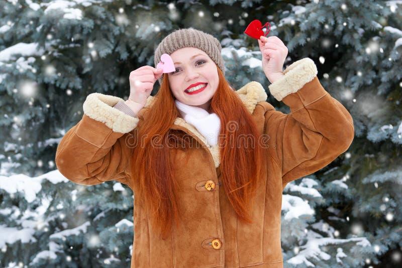 冬天室外摆在的与心脏形状玩具,假日概念,多雪的冷杉木美丽的妇女在森林,长的红色头发里,佩带 图库摄影
