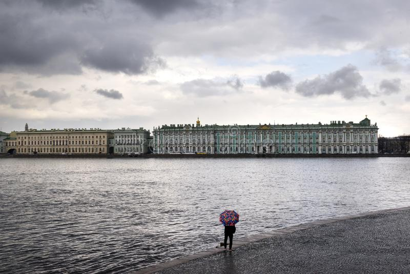 冬天宫殿和内娃河在圣彼德堡,有一把伞的一个人的看法在内娃河在春雨中 图库摄影