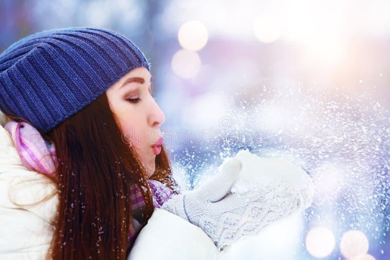 冬天少妇画象 冬天女孩吹的雪 秀丽快乐的少年式样女孩获得乐趣在冬天公园 免版税库存图片