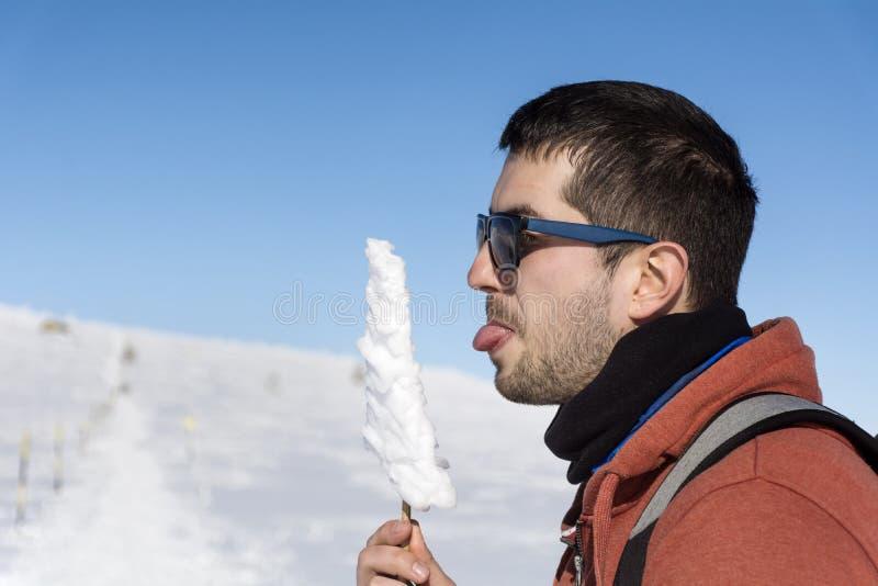 冬天山的年轻人与冰柱在手上 库存图片