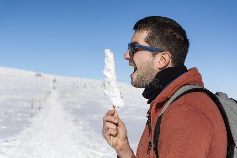 冬天山的年轻人与冰柱在手上 免版税库存图片
